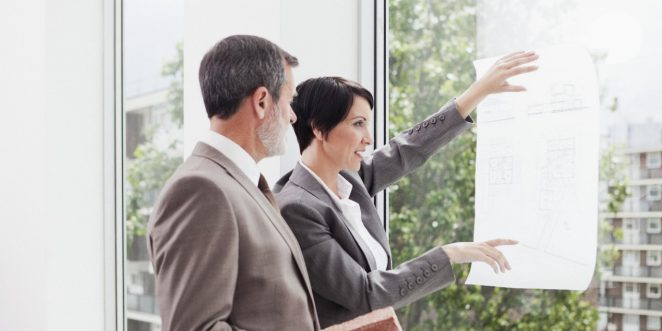 Business people looking at a blueprint held against a big window. Woman pointing at blueprint detail, man holding a brick.